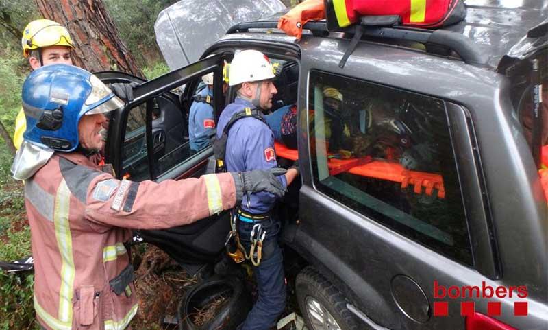 Los bomberos sacando a la mujer del vehículo