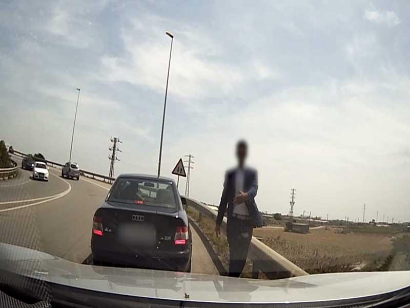 Uno de los falsos policías deteniendo un coche en la autopista